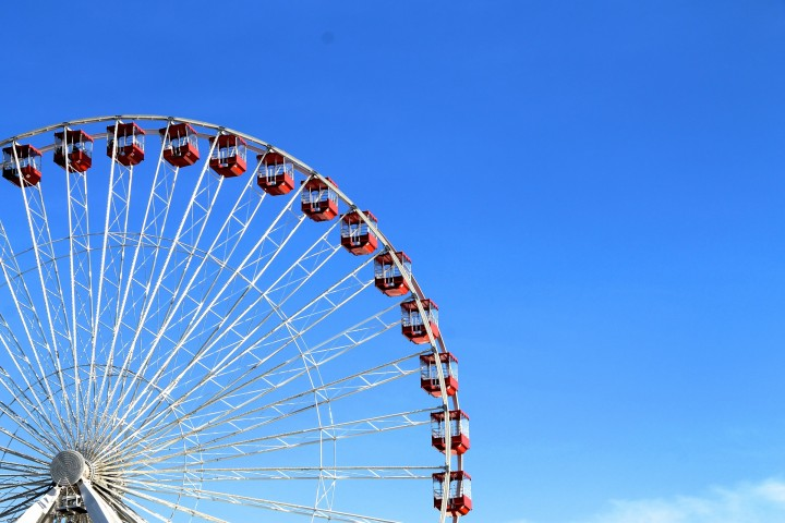 Red white ferris wheel left blue sky 720x480