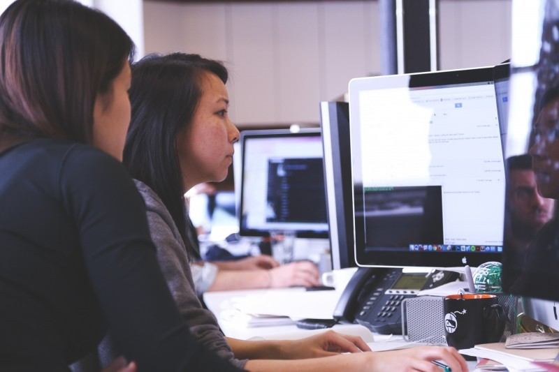 Female colleagues working on computer sitting at office desk