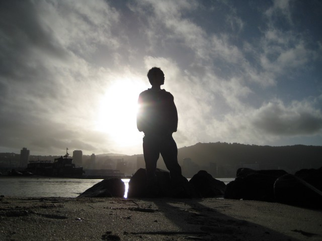 Man silhouette on rocky beach against sun 640x480